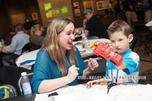 """A mother reacts to seeing her child make a fist with his new 3D printed fingers for the first time at the first e-NABLE """"Prosthetists Meets Printers"""" conference at Johns Hopkins – Sept. 2014."""